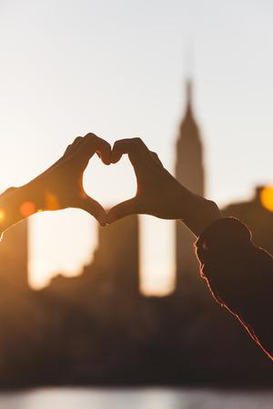 honey moon: Heart Shaped Hands at Sunset, New York Skyline on Background