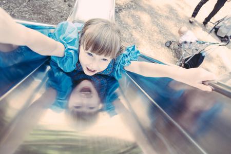 Little Girl Playing on the Slide photo