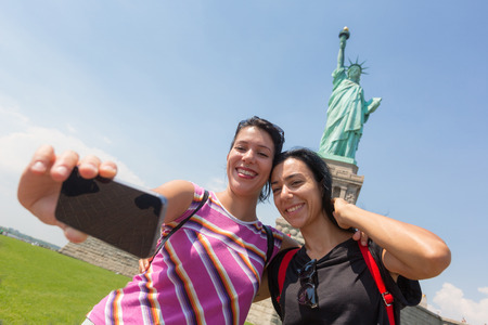 liberty island: Women Taking a Selfie with Statue of Liberty on Background Stock Photo