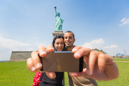 Couple Taking a Selfie with Statue of Liberty on Background photo