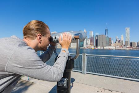 Young Man Looking through Binoculars in New York photo