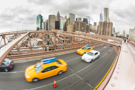 taxi famous building: Traffic on Brooklyn Bridge, Lower Manhattan in Background Stock Photo