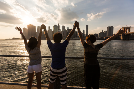 sunset city: Happy Japanese Tourists with Raised Arms in New York Stock Photo