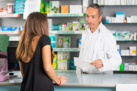 Pharmacist and Client in a Drugstore photo