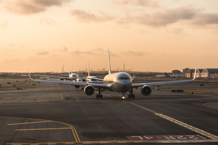 jfk: NEW YORK, USA - SEPTEMBER 10, 2014: American Airlines airplanes waiting to take off from JFK Airport. New York city skyline on background.