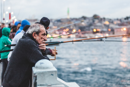 ISTANBUL, TURKEY - OCTOBER 25, 2014: Elderly man looking at fishermen fishing on Galata Bridge on a rainy day. Editorial