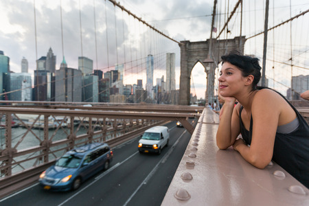 city people: Happy Young Woman on Brooklyn Bridge