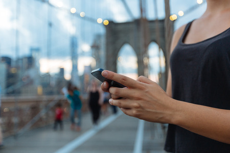 new message: Young Woman Using Smart Phone on Brooklyn Bridge