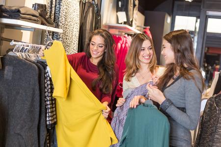 comprando zapatos: Tres mujeres en una tienda de ropa