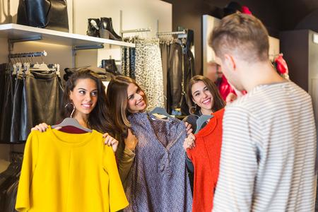 choosing clothes: Man Helping Three Women Choosing New Clothes