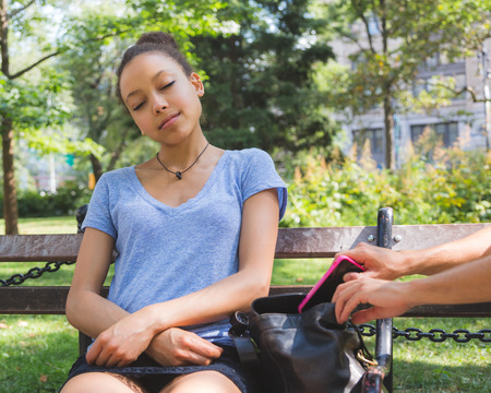 thievery: Pickpocket in Action at Park Stock Photo