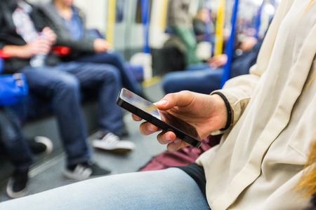 trains: Young Woman using Smart Phone in London Tube Stock Photo