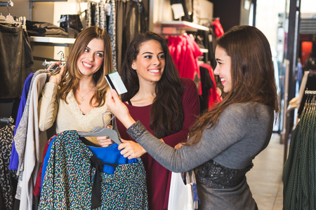 bancomat: Happy Women with Credit Card in a Clothing Store Stock Photo