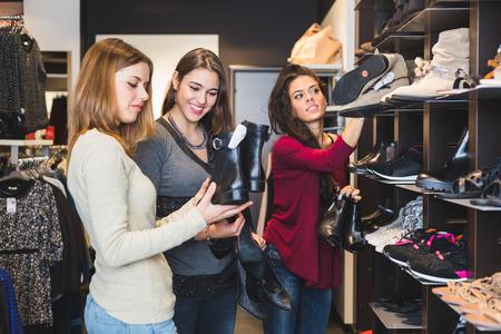 comprando zapatos: Mujeres que compran zapatos en una tienda
