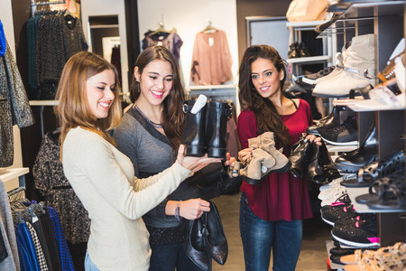 choosing clothes: Women Buying Shoes in a Store Stock Photo