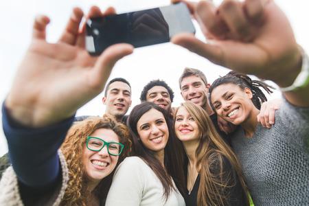 Grupo multiétnico de amigos tomando Autofoto en el Parque Foto de archivo - 34188632