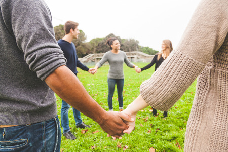 integrated groups: Multiethnic Group of Friends Holding Hands in a Circle Stock Photo