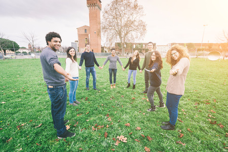 integrated groups: Multiethnic Group of Friends Giving a Hand Stock Photo