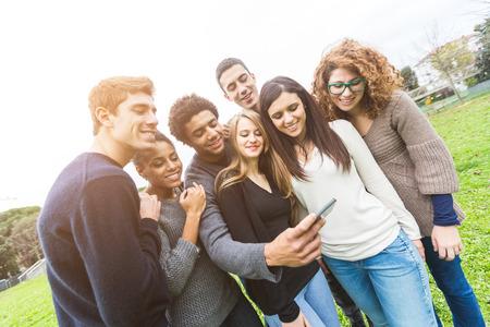 razas de personas: Grupo multi�tnico de amigos mirando el tel�fono m�vil Foto de archivo