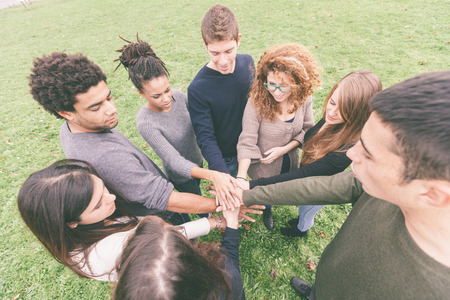 integrated groups: Multiracial Group of Friends with Hands in Stack, Teamwork