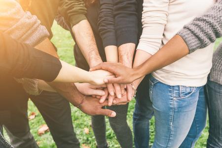 tomados de la mano: Grupo multirracial de amigos con las manos en la pila, Trabajo en equipo