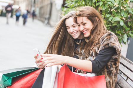 Mujeres felices con el teléfono inteligente y bolsos de compras Foto de archivo - 34384116
