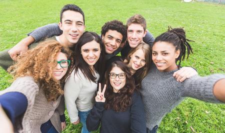 Grupo multiétnico de amigos tomando Autofoto en el Parque Foto de archivo - 34384119