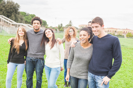 integrated groups: Multiethnic Group of Friends at Park Stock Photo