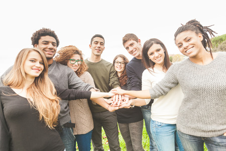 people holding hands: Multiracial Group of Friends with Hands in Stack, Teamwork