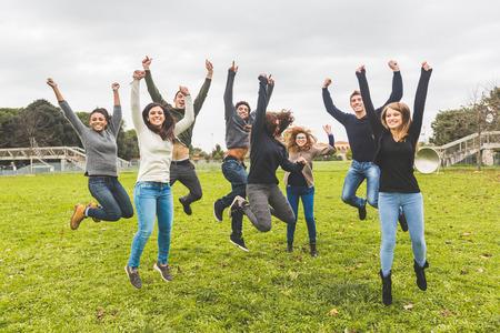 Multi-etnische groep van vrienden springen Together Stockfoto