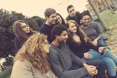 integrated groups: Multiethnic Group of Friends Looking at Mobile Phone Stock Photo