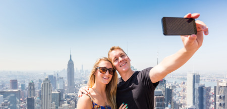 panorama city panorama: Young Couple Taking Selfie with New York on Background Stock Photo