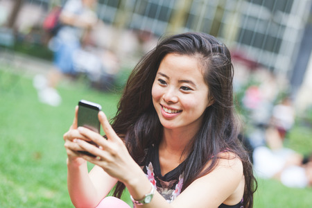 bryant park: Asian Girl Typing on Smart Phone at Park
