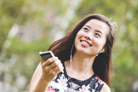 Asian Girl Listening Music at Park Stock Photo