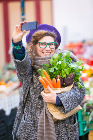 Young Woman Taking a Selfie at Vegetables Market photo
