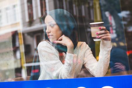 カフェの窓の後ろにイスラム教徒の女性