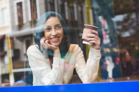 カフェで携帯電話で話しているイスラム教徒の女性