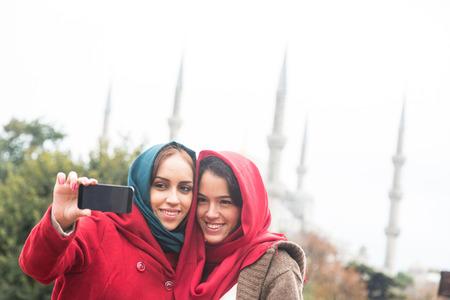 est: Arab Women Wearing Veil Taking Selfie in Istanbul