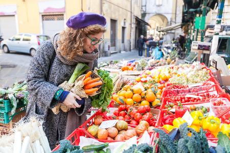 Jonge vrouw het kopen groenten op de lokale markt Stockfoto