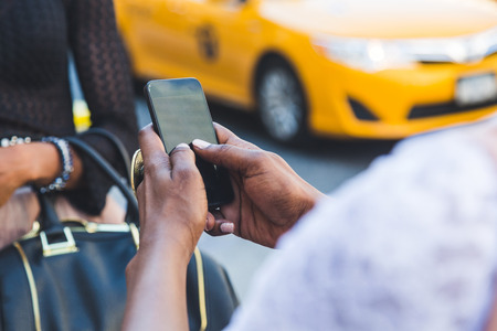 taxis: Two Beautiful Black Woman Using Smart Phone in New York Stock Photo