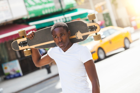 longboard: Black Boy Walking in the City Holding Longboard