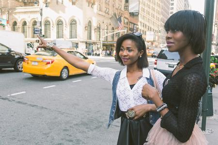 persona llamando: Dos Hermosa Mujer Negro Llamar a un taxi en Nueva York Foto de archivo
