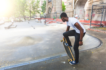 longboard: Black Boy Skating at Park with Longboard Stock Photo