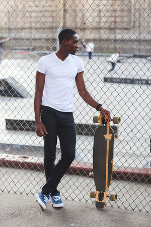 longboard: Black Boy with Longboard at Park