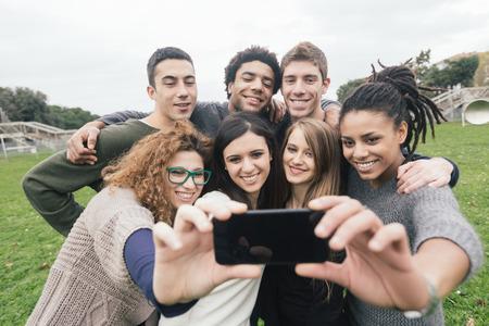 juventud: Grupo multiétnico de amigos tomando Autofoto en el Parque