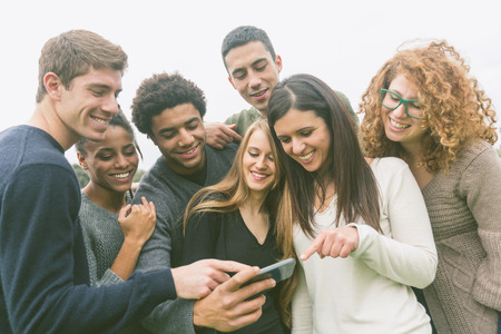 adult students: Multiethnic Group of Friends Looking at Mobile Phone Stock Photo