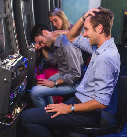 maquinas tragamonedas: Grupo de amigo Jugando con Slot Machines