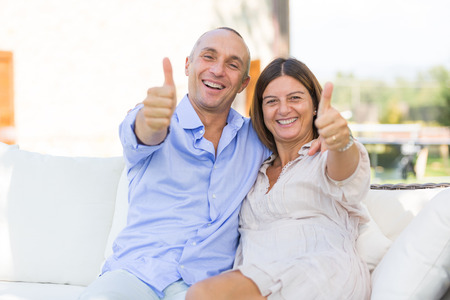 looking up: Mature Couple Showing Thumbs Up Stock Photo