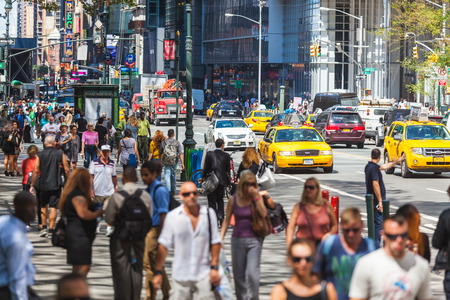 28: NEW YORK, USA - AUGUST 28, 2014: Crowded 5th Avenue with tourists on sidewalk and yellow cabs on the street. Editorial