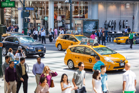NEW YORK, USA - AUGUST 28, 2014: Crowded 5th Avenue with tourists on sidewalk and yellow cabs on the street. Editorial